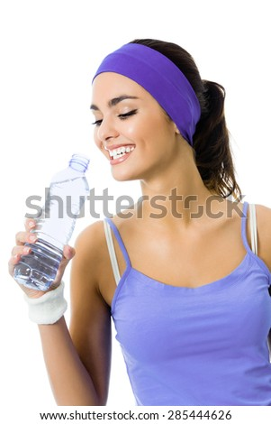 Happy smiling young woman in violet sportswear drinking water, isolated over white background. Young female fitness instructor or personal trainer at studio shot. Health, beauty and fitness concept.  - stock photo