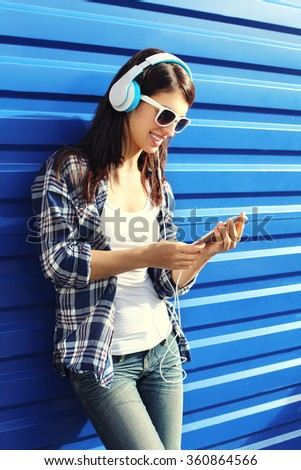 Happy smiling young woman listens to music in headphones and using smartphone over blue background - stock photo