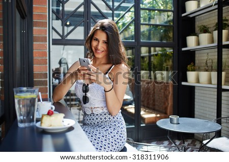 Happy smiling young woman makes on-line shopping with internet on mobile phone application, female tourist browsing in coffee shop, attractive girl hold smart phone while laughing and looking to you - stock photo