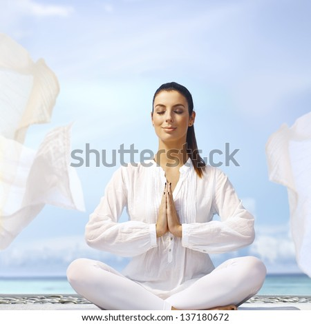 Happy smiling young woman meditating eyes closed on the coast in white outfit. - stock photo