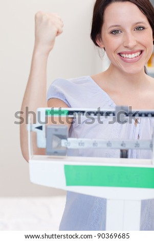 Happy smiling young woman on the scale - stock photo