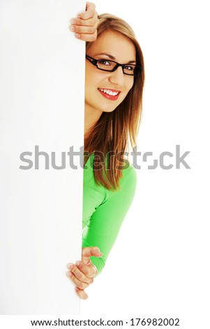Happy smiling young woman showing blank signboard, over white background  - stock photo