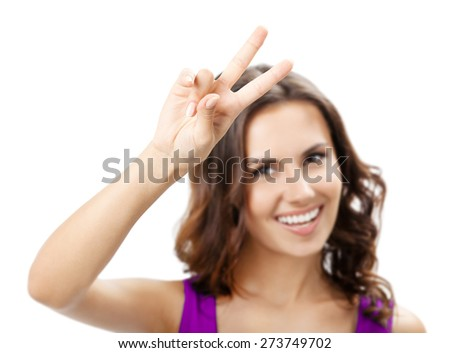 Happy smiling young woman showing two fingers or victory gesture, isolated against white background. Selective focus on hand. - stock photo