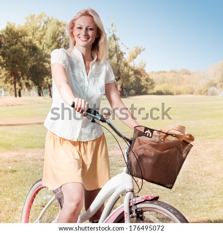 Happy smiling young woman with a bicycle in the park.