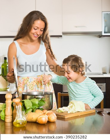 Happy smiling young woman with little girl cooking at home kitchen