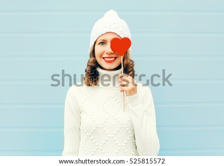 Happy smiling young woman with red lips holds lollipop heart wearing knitted hat sweater over blue background