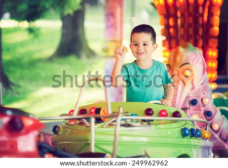 Happy smilling boy driving boat toy at an amusement park. Toned photo. - stock photo