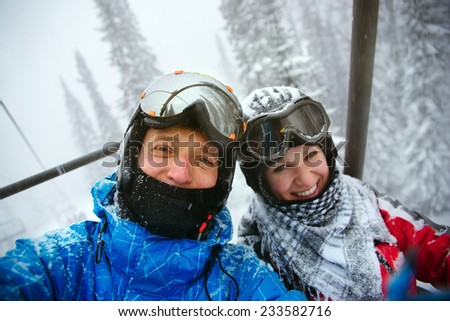 Happy snowboarders  in winter mountains - stock photo