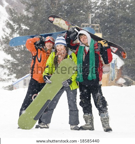 Happy snowboarding team in winter mountains, health lifestyle (series Sport, Extreme, Mountains, Horses and Teenagers) - stock photo