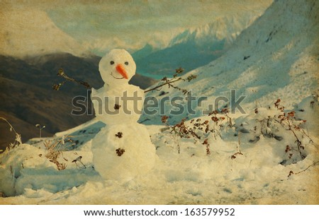 Happy snowman in mountains. Photo in retro style. added paper texture.  - stock photo