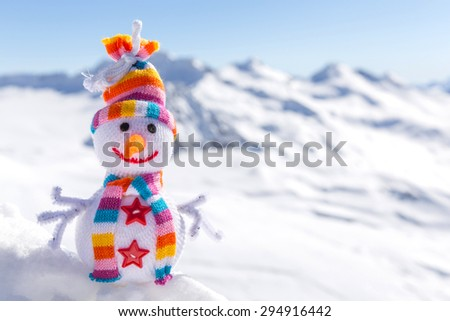 Happy snowman in mountains standing in winter landscape - stock photo