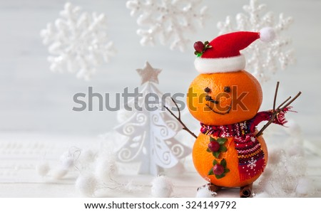 Happy snowman made out of tangerines,clove and winter berries - stock photo