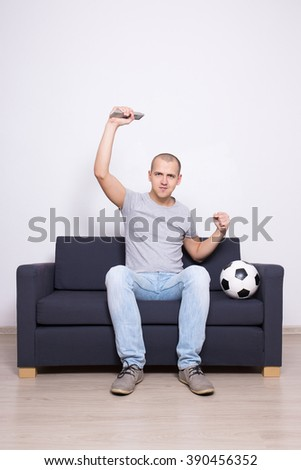 happy soccer fan watching game on television - stock photo