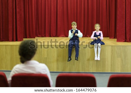 Happy son and daughter sit on stage with red curtains and mother looks at them. Focus on children. - stock photo