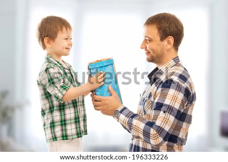 Happy son gives his father gift. Fathers day, family holiday, vacation. - stock photo