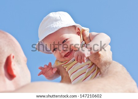 happy son in his father's arms on a blue sky background