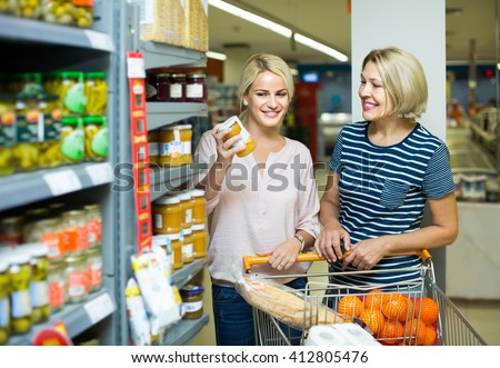 happy spanish girl and mature woman purchasing canned food at supermarket - stock photo