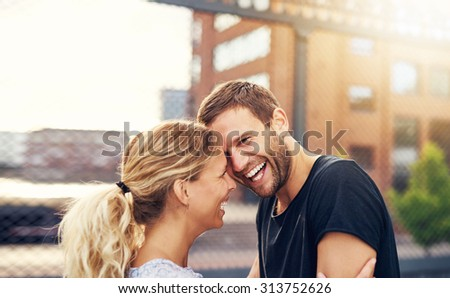 Happy spontaneous attractive young couple share a good joke laughing uproariously and hugging each other outdoors in an urban environment - stock photo