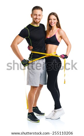 Happy sport couple - man and woman with measuring tape on the white background - stock photo