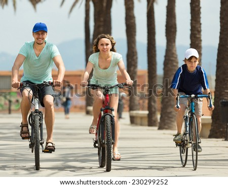 Happy sports family of three with bicycles outdoors - stock photo