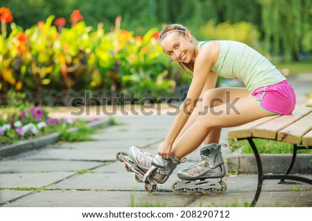 Happy sports woman is sitting on a bench in a park and putting on inline roller skates. Close up. Sport lifestyle. - stock photo