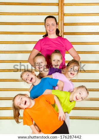 Happy sporty children with coach in gym - stock photo