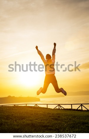Happy sporty woman jumping and raising arms towards golden beautiful sunset and sea. Female athlete celebrating sport success and goals. Healthy lifestyle concept. - stock photo