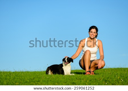 Happy sporty woman taking a  running and exercising rest with her dog. Female athlete enjoying outdoor with her pet. - stock photo