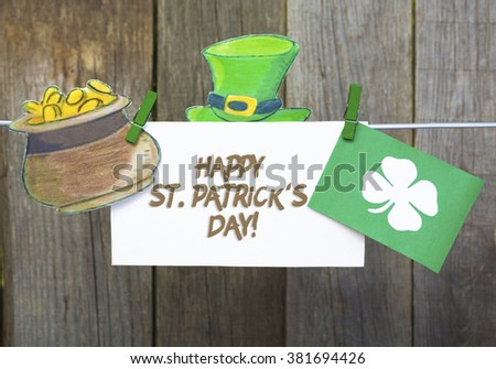happy St Patrick's Day card, March 17, with Leprechaun hat and pot of gold, on  pegs ( clothespin ) wooden background. - stock photo
