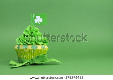 Happy St Patrick's Day green cupcakes with shamrock flags and leprechaun hat against a green background - stock photo