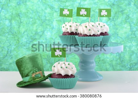 Happy St Patricks Day cupcakes with shamrock flags and green leprechaun hat against a green background on a white wood table.  - stock photo