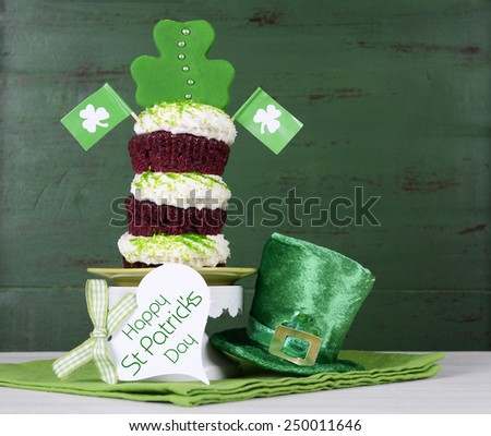 Happy St Patricks Day triple layer cupcake with shamrock decorations and leprechaun hat against a vintage style green wood background. - stock photo