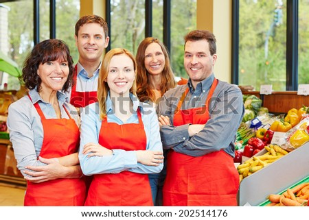 Happy staff team with men and women in a supermarket - stock photo