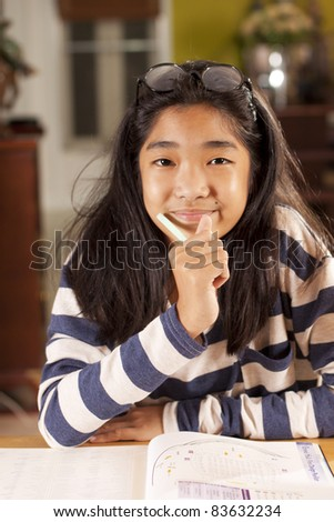 happy student, a girl smiling having pencil and eyeglass at home school. - stock photo