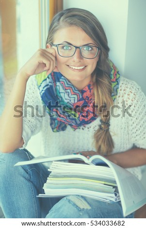 Happy student girl sitting with pile of books