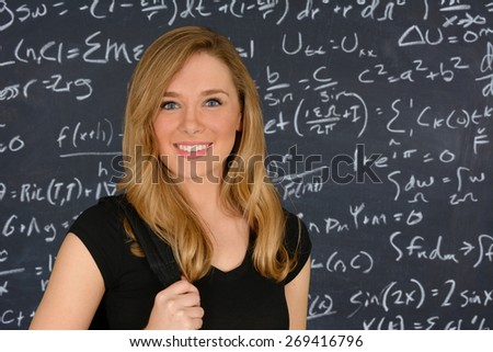 Happy student girl standing in front of the blackboard