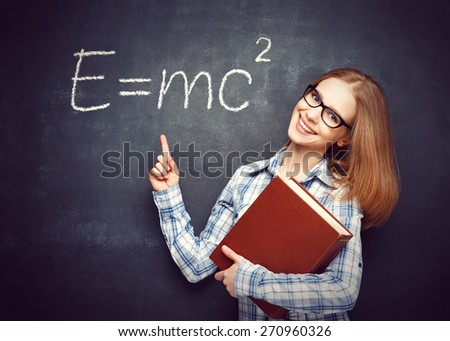 Happy student girl with book and glasses has written on the blackboard formula in physics - stock photo