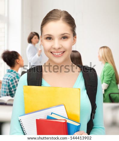 happy student girl with school bag and notebooks at school - stock photo