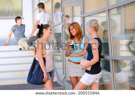 Happy student girls chatting together outside college friends in background - stock photo