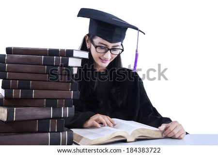 Happy student in graduation cap is reading books. isolated on white - stock photo