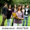 happy student outdoors with a group of friends behind her - stock photo