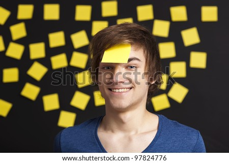 Happy student with a reminder on the head, and with more yellow paper notes in the background - stock photo