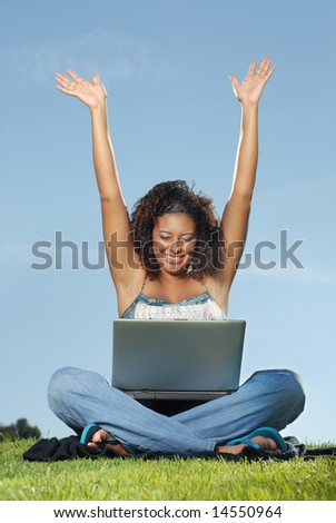 Happy student with raised arms at a laptop - stock photo