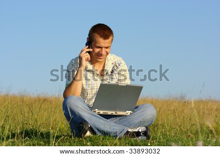 Happy student working with laptop and talking to a cell phone on green meadow, summer sunny day - stock photo