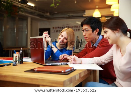 Happy students doing homework with laptop together - stock photo