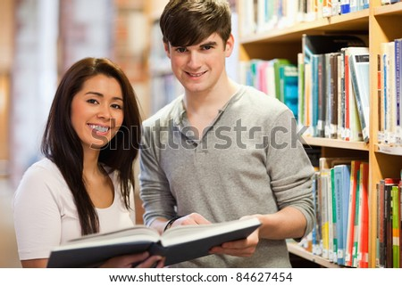 Happy students holding a book in a library - stock photo