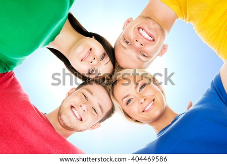 Happy students in colorful clothing standing together over blue sky background - stock photo