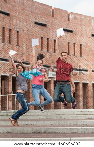 Happy students jumping in the air holding exam in school - stock photo