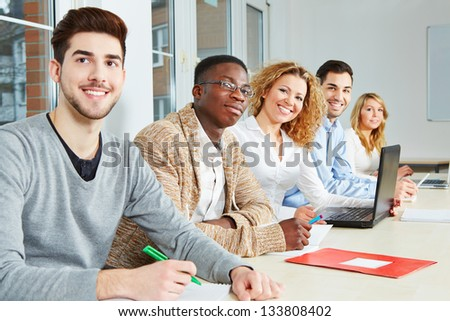 Happy students learning in class in a university - stock photo