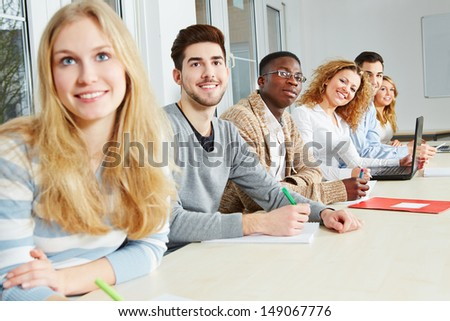 Happy students learning together in a university seminar - stock photo